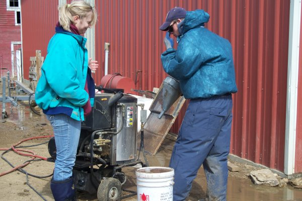 Desiree & Peder refill the fuel in the power washer